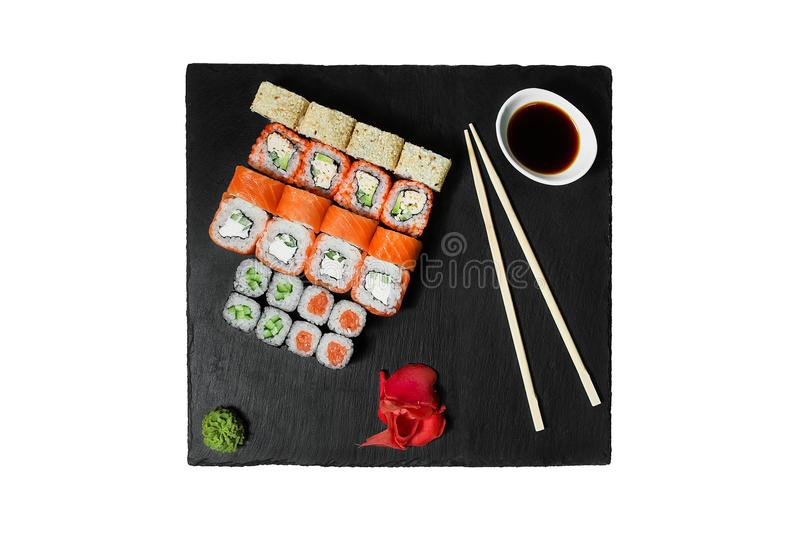 Big roll set. Different sushi rolls with cucumbers avocado salmon, eel, caviar, cream cheese served on black graphite plate stock images