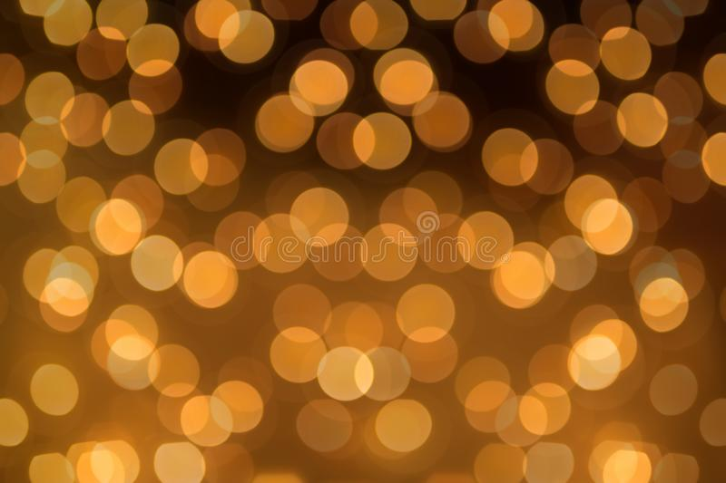 Big round Bokeh in golden yellow on dark brown background. Abstract Blurred circles stock photography