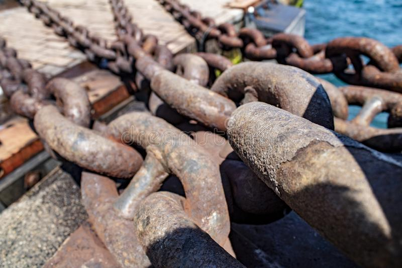 Big rusty chain. Close-up. Used on ships iron old heavy metal industrial background steel boat chains rough strong marine nautical sea blue abstract black stock image