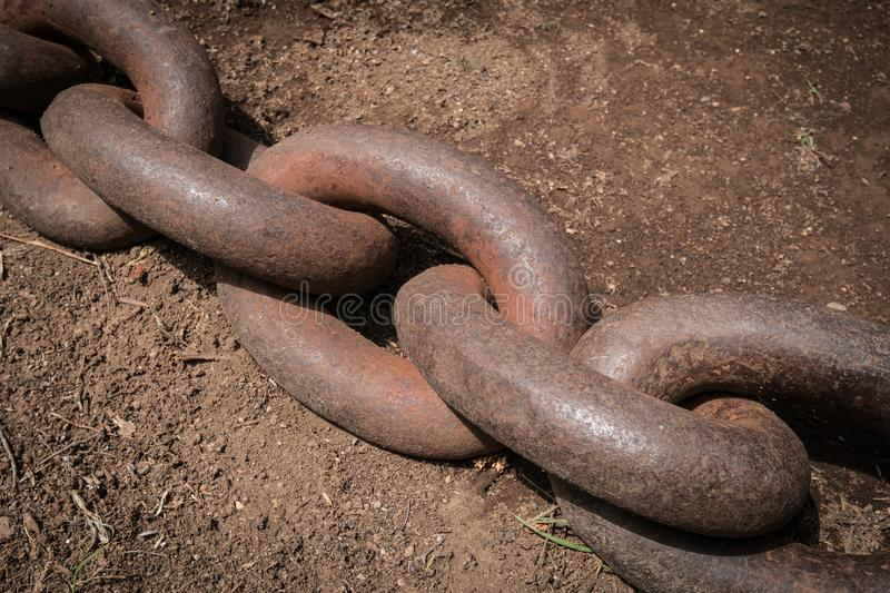 Big rusty chain on floor closeup - anchor chain royalty free stock photo