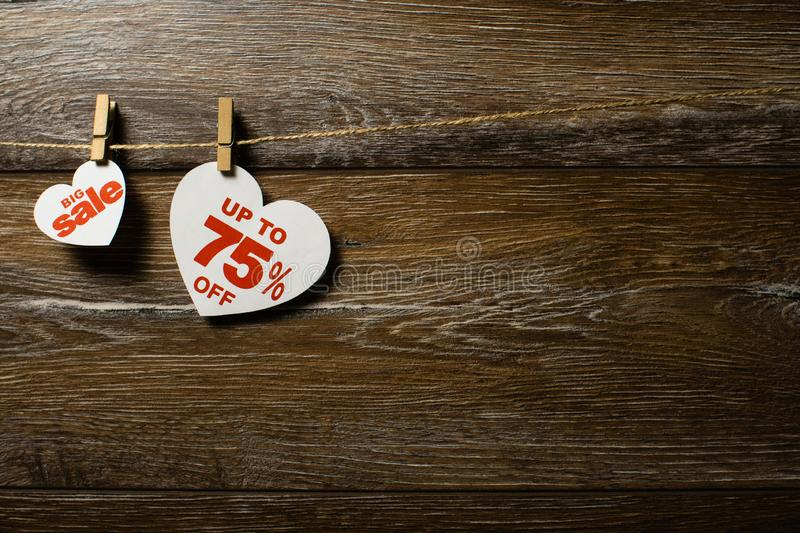 Big sale on hearts hanging on rope with clothespins over the wooden background. Seventy-five percent discount promotion written on. White heart stock photo