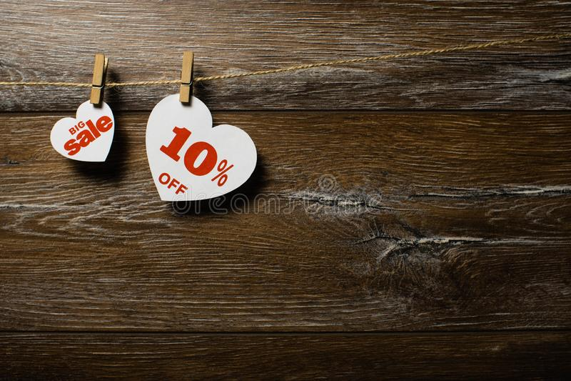 Big sale on hearts hanging on rope with clothespins over the wooden background. Ten percent discount promotion written on heart royalty free stock photos