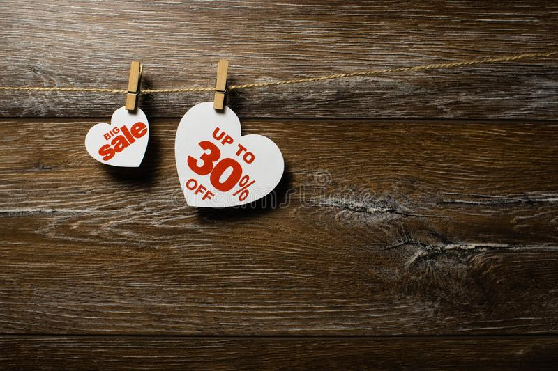 Big sale for valentine day. Thirty percent discount. Big sale on hearts hanging on rope with clothespins over the wooden background. Thirty percent discount royalty free stock image