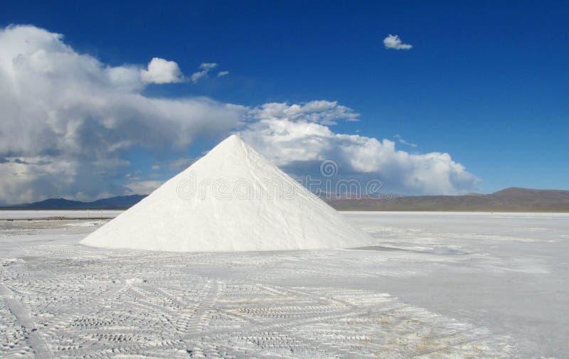 Big salt pile on Salar. Salt pile on Salar, salt production. Salt lake plato, flat plaine covered with white salt and blue water. Mountains on horizont. Uyuni royalty free stock photos