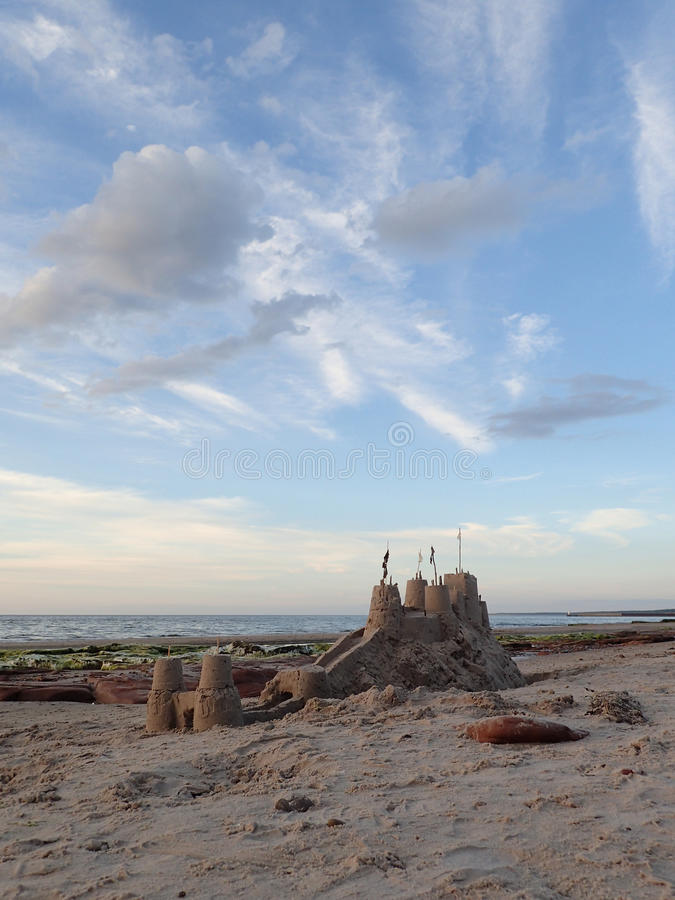 Big sandcastle on mound with moat, & cloudy blue sky. stock images