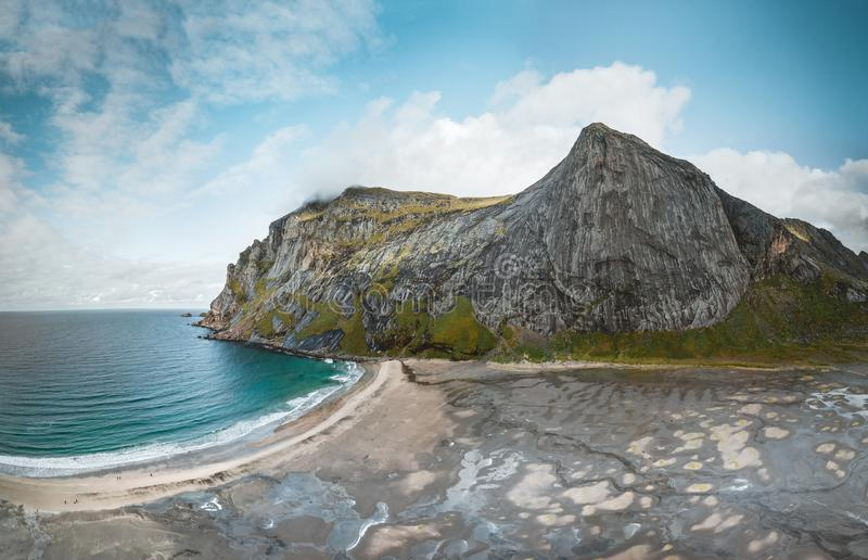 Big sandy aerial drone panorama of Bunes beach in bay surrounded by steep mountains in sunset with dramatic colorful sky royalty free stock images
