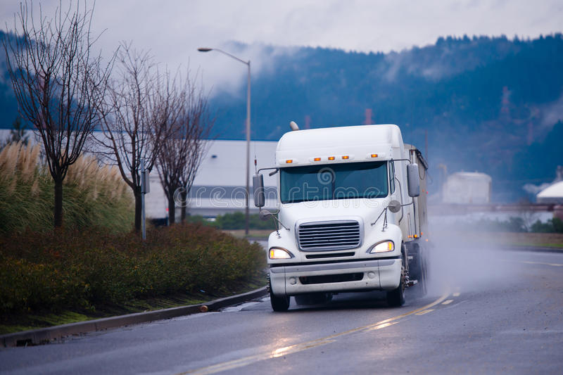 Big semi truck on bend road in cloud storm dust. Big white semi truck with a trailer carrying goods covered Tharp at the turn of the road in a cloud of dust stock image