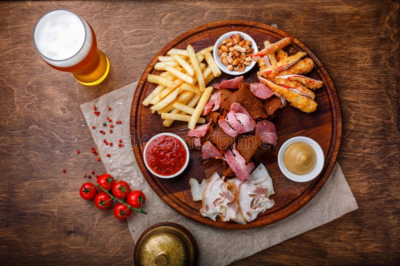 Big set of snacks for beer or alcohol and it includes smoked pork meat, french fries, fried bread, crab sticks and nuts royalty free stock photos