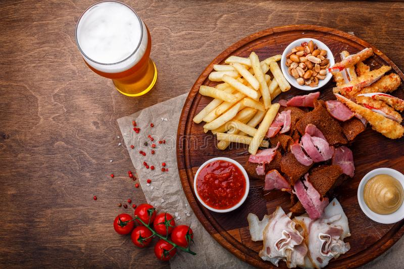 Big set of snacks for beer or alcohol and it includes smoked pork meat, french fries, fried bread, crab sticks and nuts stock photography
