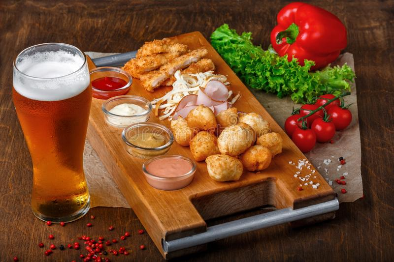 Big set of snacks for beer it includes fried cheese balls, pigtail cheese, ham and crab sticks on a wooden board royalty free stock images