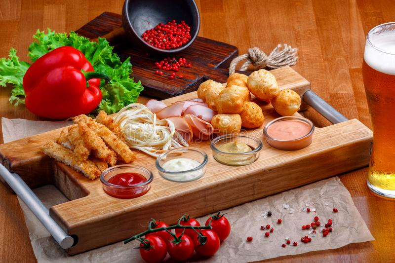 Big set of snacks for beer it includes fried cheese balls, pigtail cheese, ham and crab sticks on a wooden board stock photo