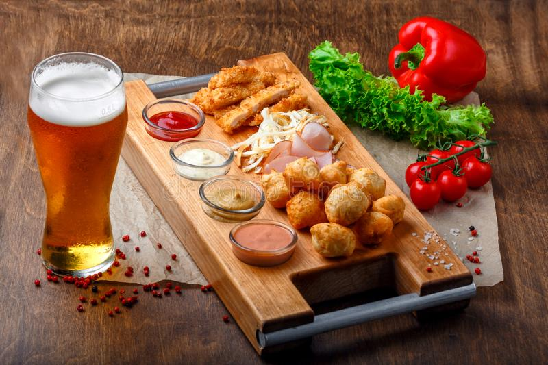 Big set of snacks for beer it includes fried cheese balls, pigtail cheese, ham and crab sticks on a wooden board royalty free stock image