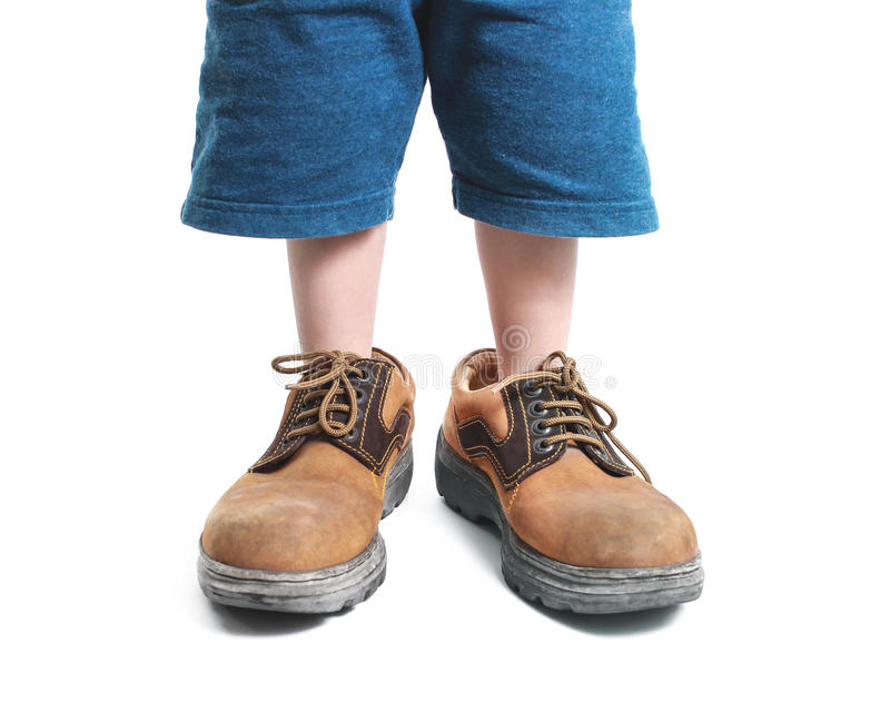 Big shoes. Kid in big shoes on white background stock photography