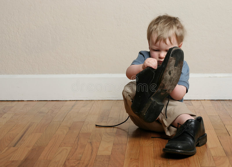 Big shoes, little feet. Small child tries to put on his father's shoes; father's day; childhood