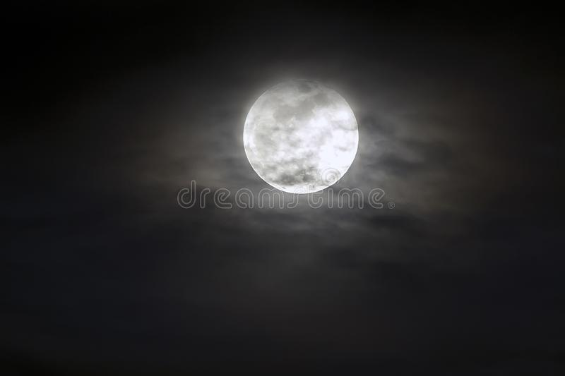 Big silver glowing Moon close-up on dark blue sky with scattered clouds. stock images
