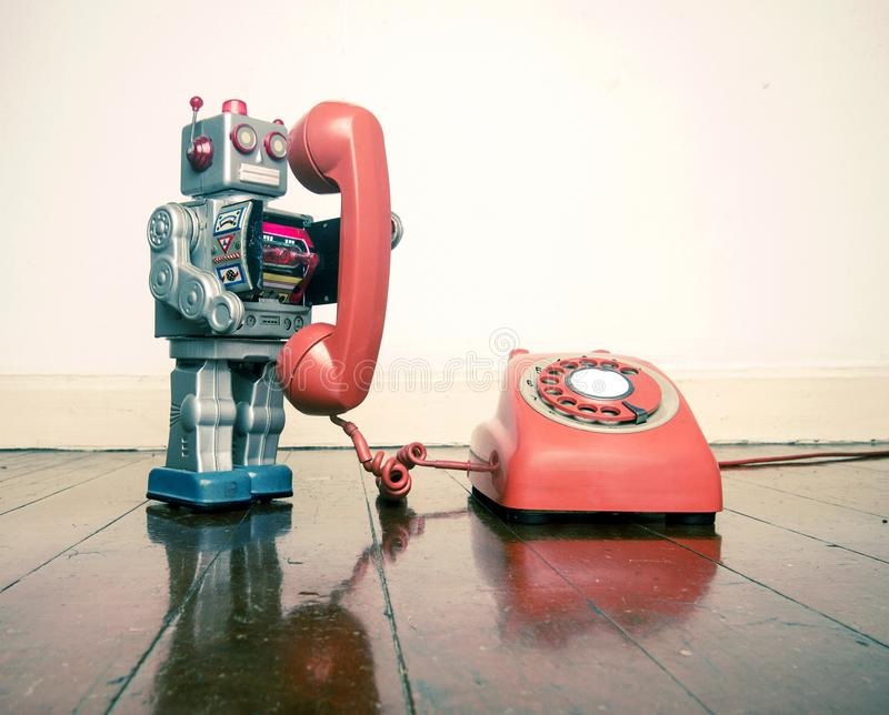 Big silver robot toy on the phone standing on an old wooden floor t. Oned image royalty free stock images