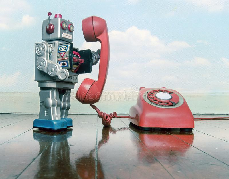 Big silver robot toy on the phone. Standing on an old wooden floor toned image royalty free stock photo