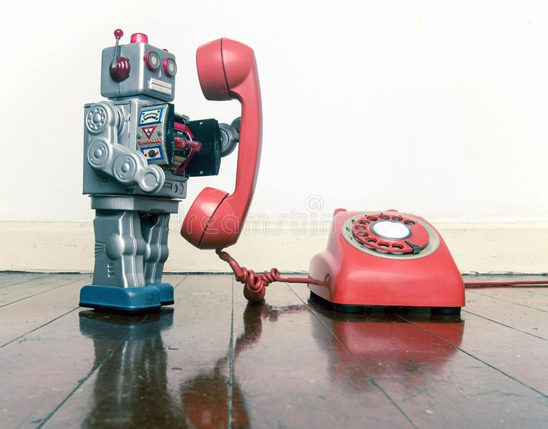 Big silver robot toy on the phone. Standing on an old wooden floor toned image royalty free stock images
