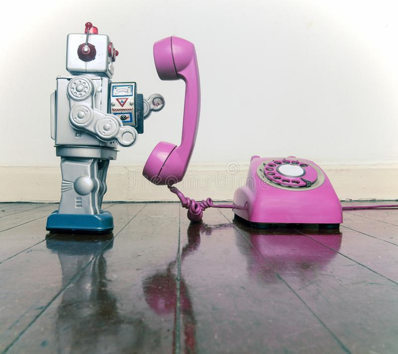 Big silver robot toy on a pink phone standing. On an old wooden floor toned image stock photo