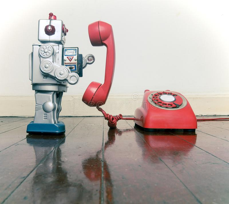 Big silver robot toy on a red phone standing. On an old wooden floor toned image royalty free stock photos