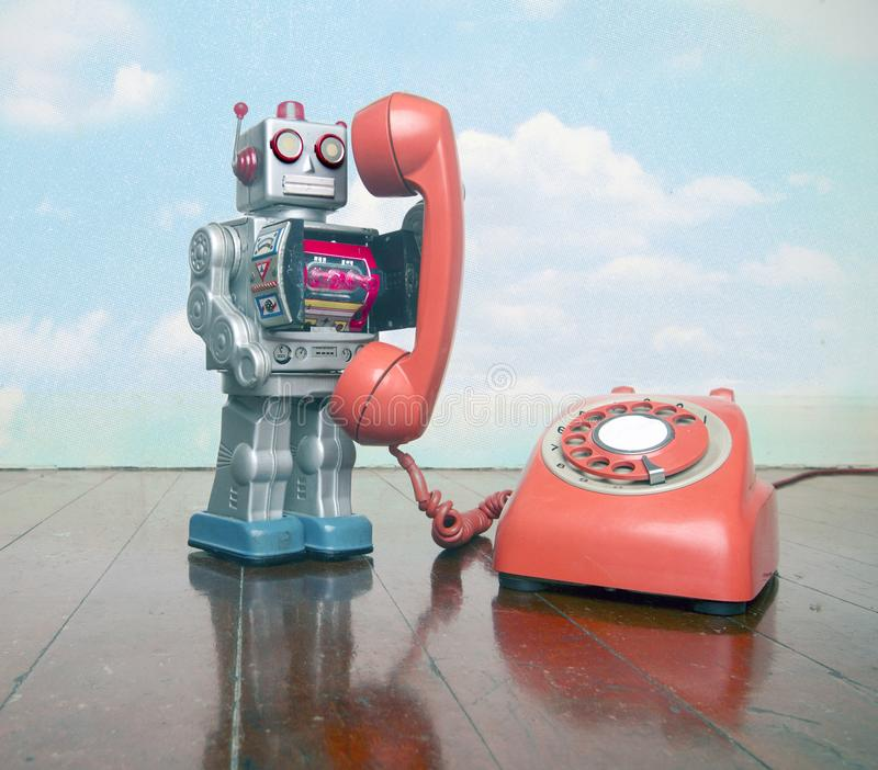 Big silver robot toy on  a red phone standing on an old. Wooden floor toned image royalty free stock images