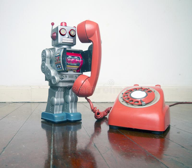 Big silver robot toy on a red phone standing on an old. Wooden floor toned image royalty free stock photo