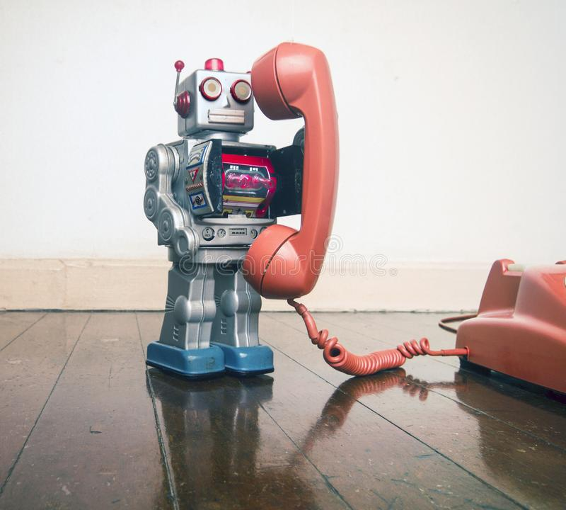 Big silver robot toy on a retyro phone standing on an old woo. Den floor toned image stock photos