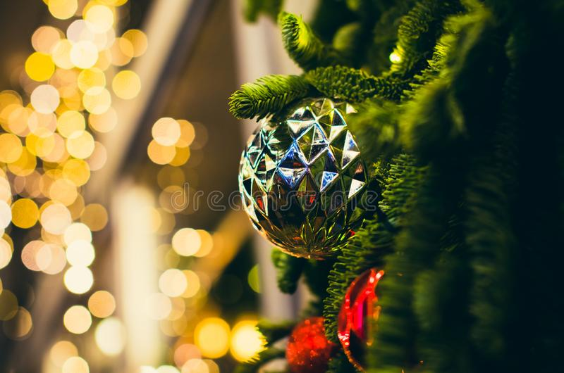 Big silver rough ball on the Christmas tree closeup with yellow bokeh stock photo