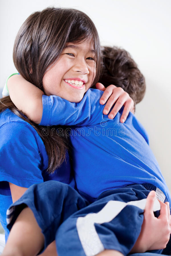 Big sister holding her disabled little brother royalty free stock photo