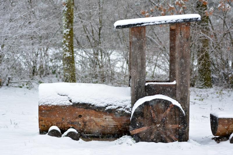 Big size wooden railway locomotive engine as part of a playground covered in snow during winter storm stock images