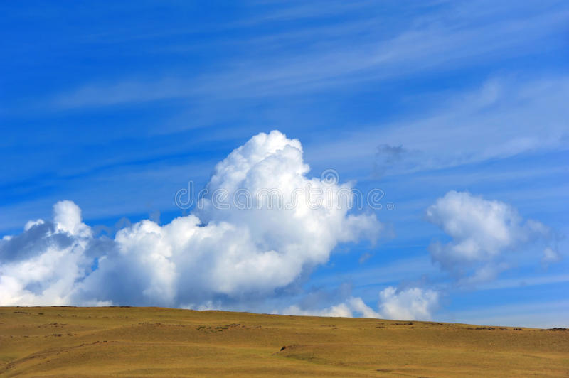 Big Sky Country. Background image shows horizon and the 'Big Sky' country or Montana. Cloud bank sits on vivid blue sky royalty free stock photo