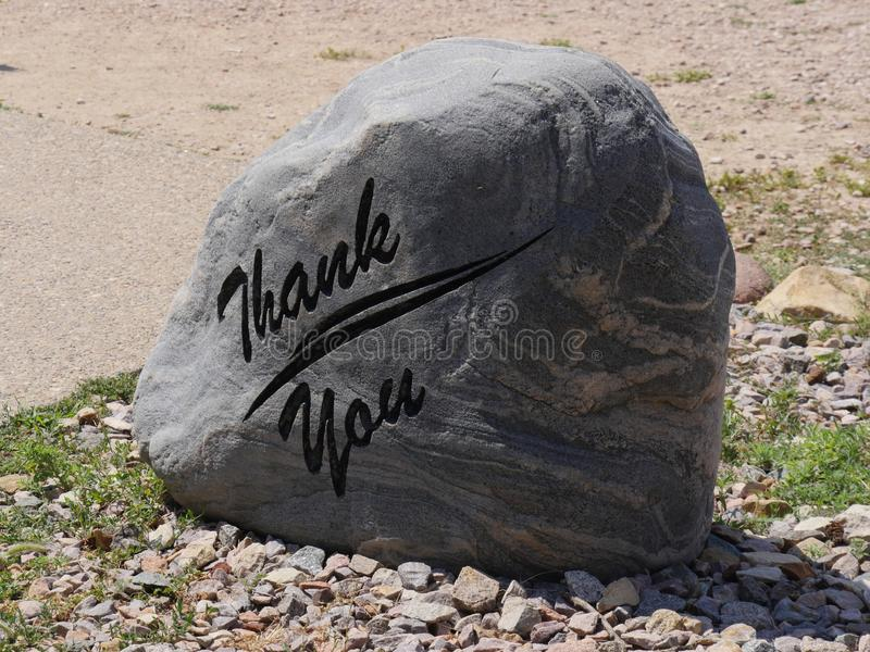 Big slab of rock. Thank You printed in a big rock at a park stock photography