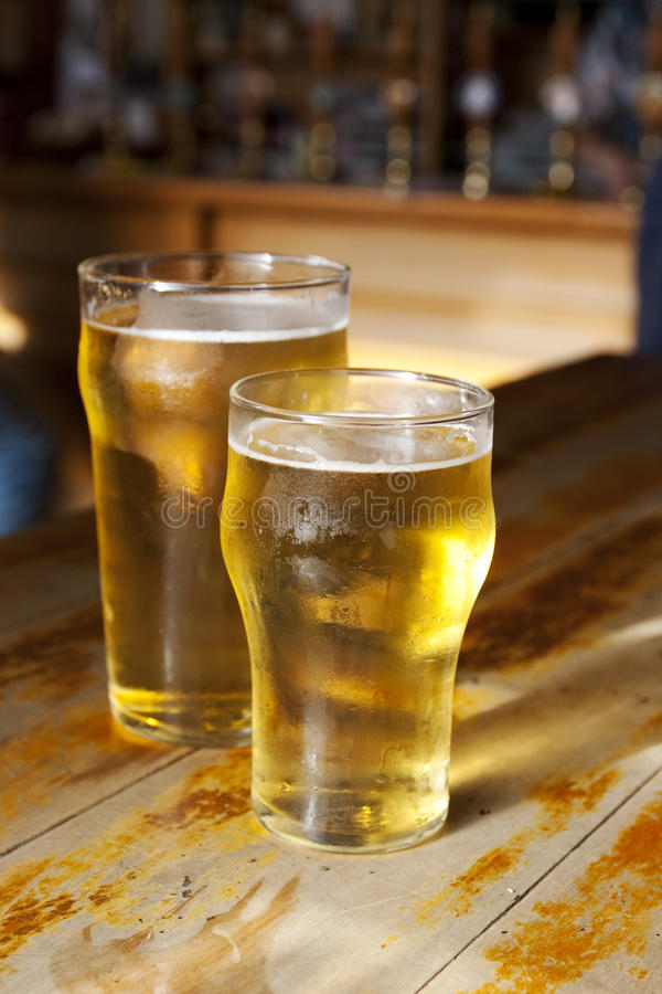 Big and small beers. Two light golden beers on a wooden bar royalty free stock photos