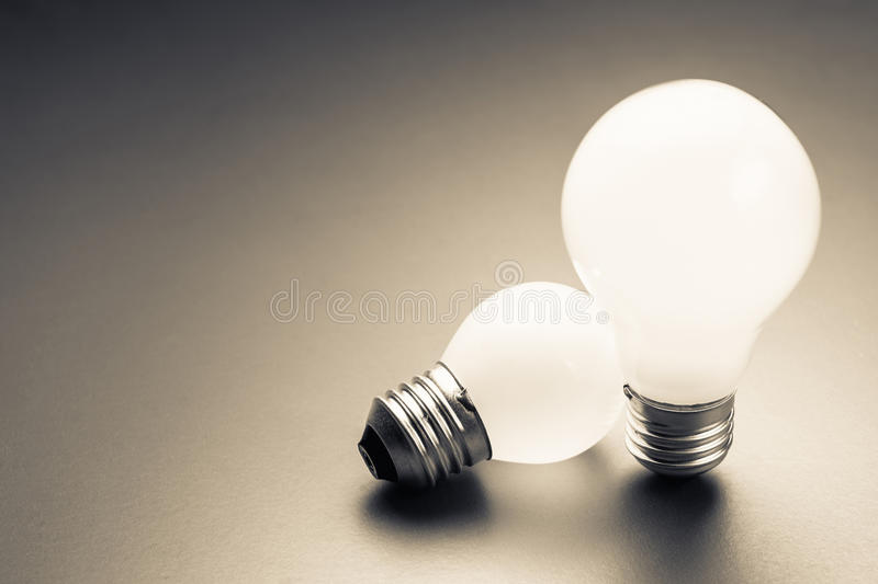 Big and Small Bulbs. Comparative big and small light bulb, small and medium sized business, coaching, training, or other comparison concept royalty free stock image