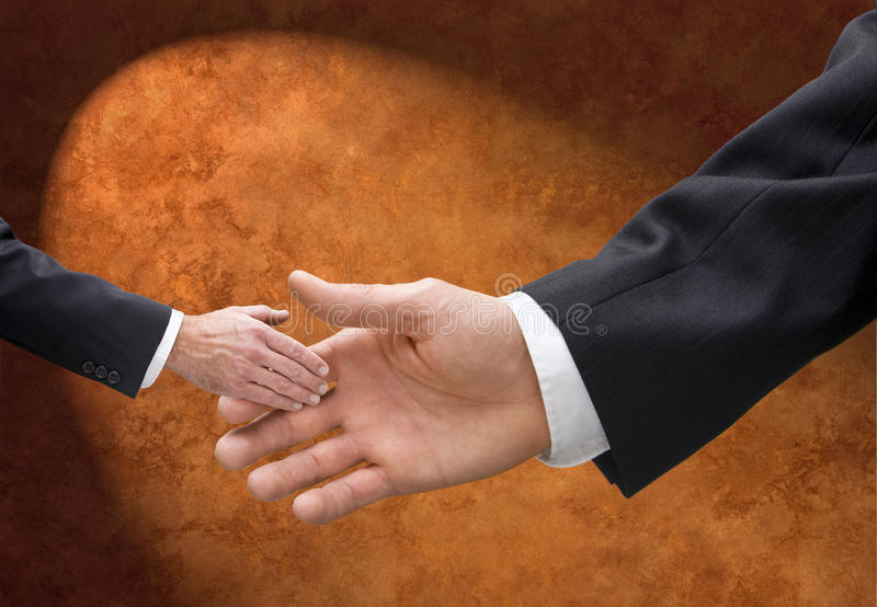 Big or Small Business Handshake. A large hand and a small hand sharing a handshake stock photos