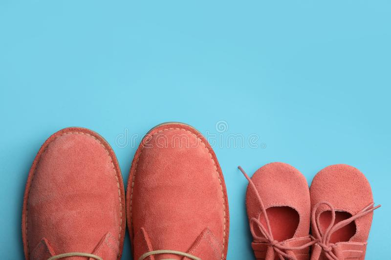 Big and small coral shoes on light blue background. Space for text. Big and small coral shoes on light blue background, top view. Space for text royalty free stock photos