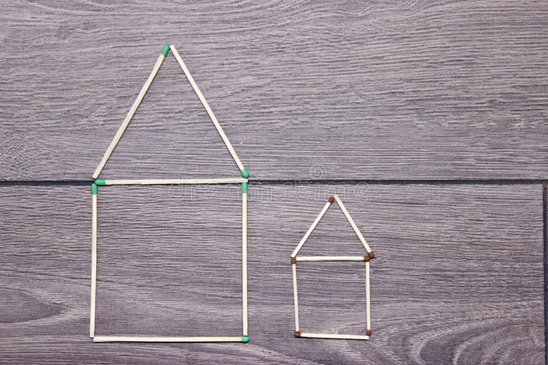 Big and small house made of matches on the floor. stock photography