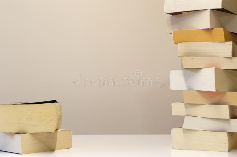 Big and small pile of books on white table. Big and small pile of books on the white table with a place for personal text in the middle royalty free stock photo