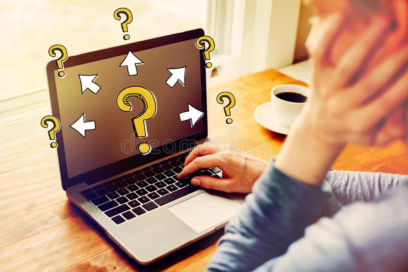 Big and small question marks with arrows with man using a laptop stock photography