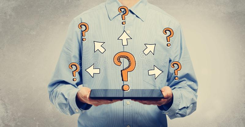 Big and small question marks with arrows with man holding a tabl royalty free stock photo