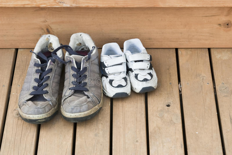 Big and small shoes on the back deck. Big and small shoes on a wooden back deck stock photo
