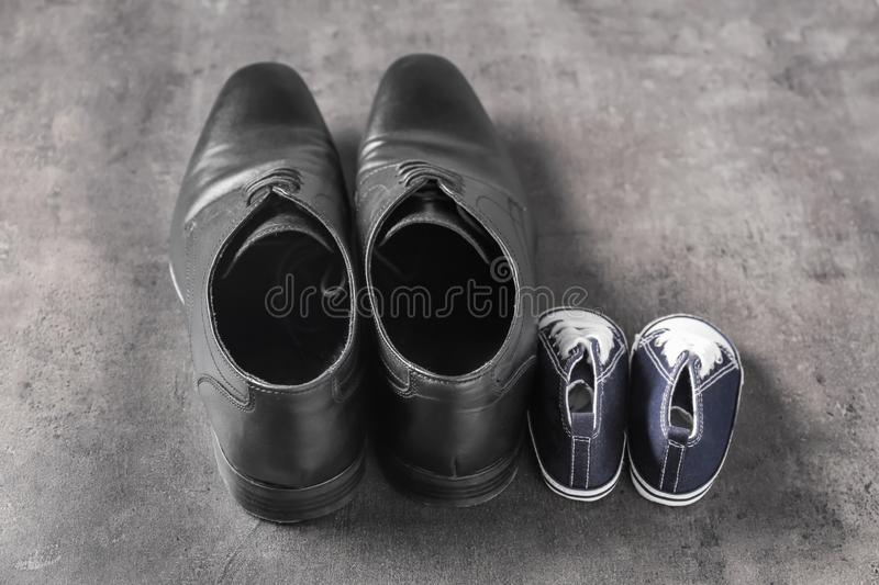 Big and small shoes on grey background. Father's day celebration royalty free stock photos