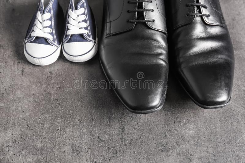 Big and small shoes on grey background. Father's day celebration stock photography