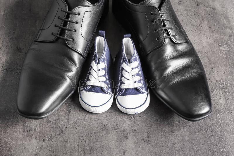 Big and small shoes on grey background. Father's day celebration royalty free stock images
