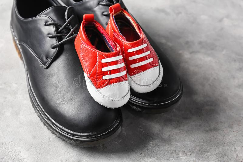 Big and small shoes on grey background. Father's day celebration stock photo