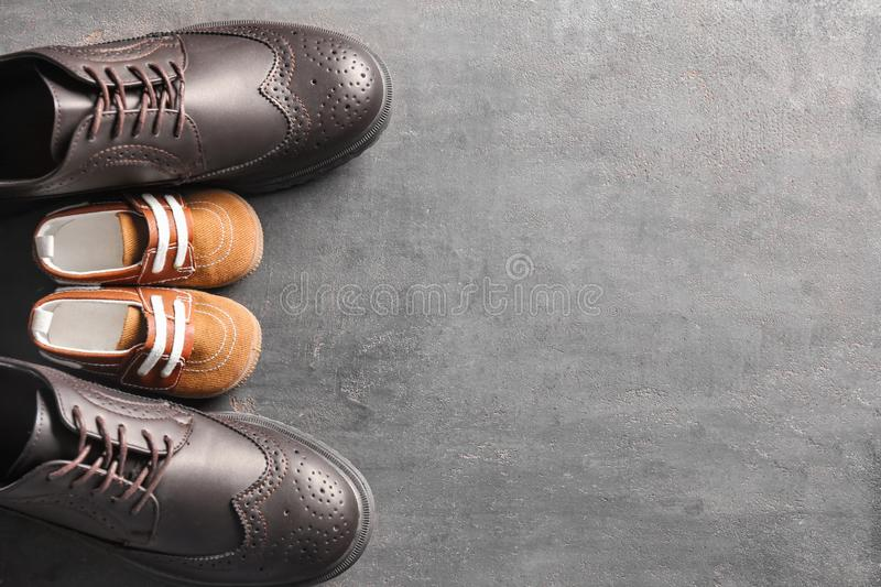 Big and small shoes on grey background. Father's day celebration stock images