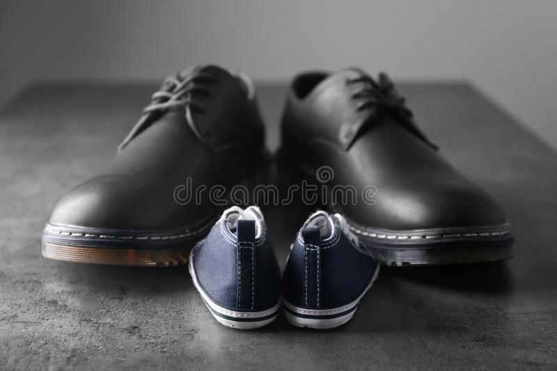 Big and small shoes on grey table. Father's day stock image