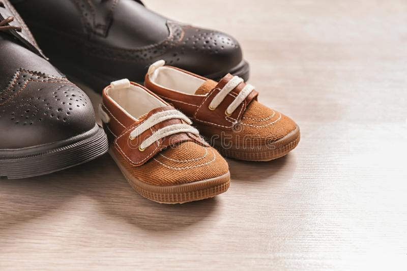 Big and small shoes on light background, closeup. Father's day stock photo