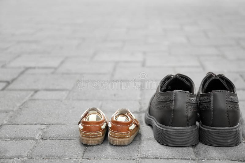 Big and small shoes on pavement outdoors. Father's day royalty free stock image