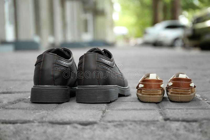 Big and small shoes on pavement outdoors. Father\'s day stock images